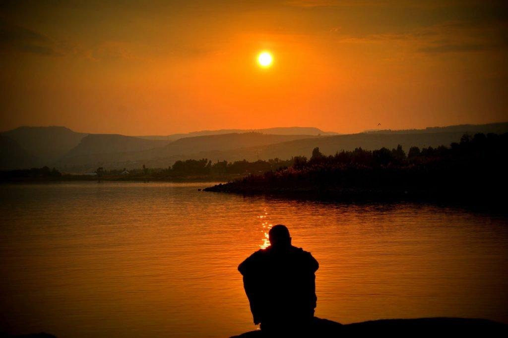una persona con adicción contempla un lago